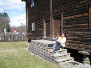 Inger Johanne nyter solen på trappen til et av de gamle husene på Domkirkeodden i Hamar