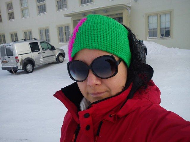 """Sofia på Svalbard utenfor restauranten """"Huset"""" der hun jobber. Foto hentet fra facebook."""