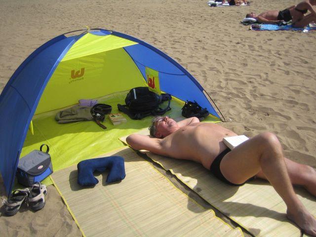 Terje nyter solen ved strandteltet vårt